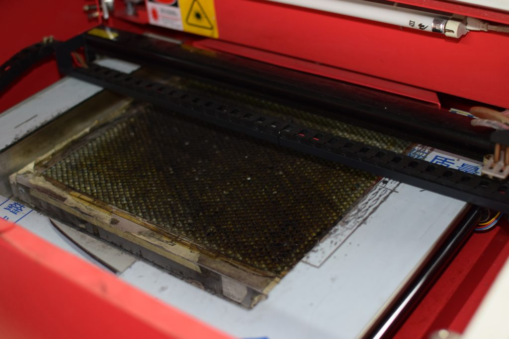 inside the laser cutter showing the dirty bed